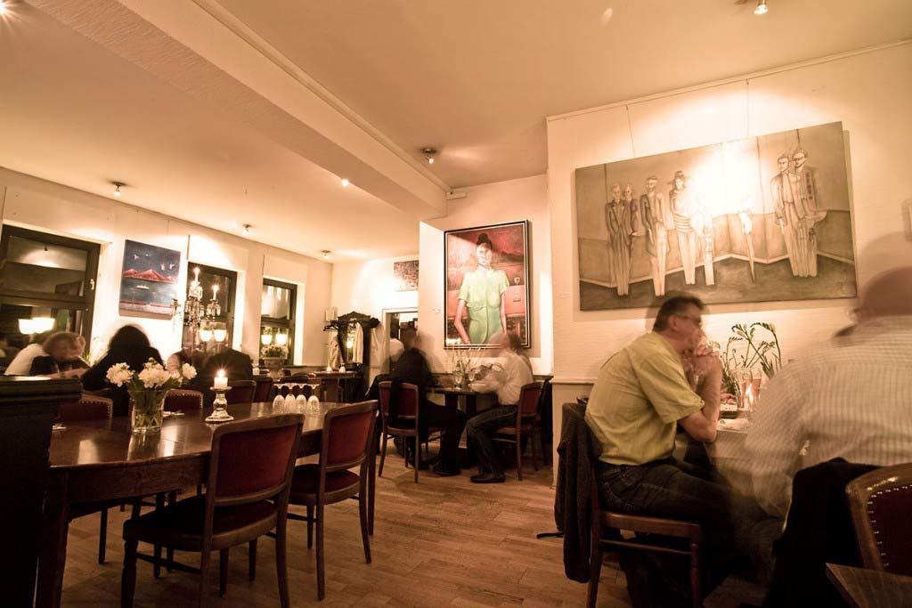 Innenansicht des Restaurants mit besetzten Tischen und vielen künstlerischen Bildern