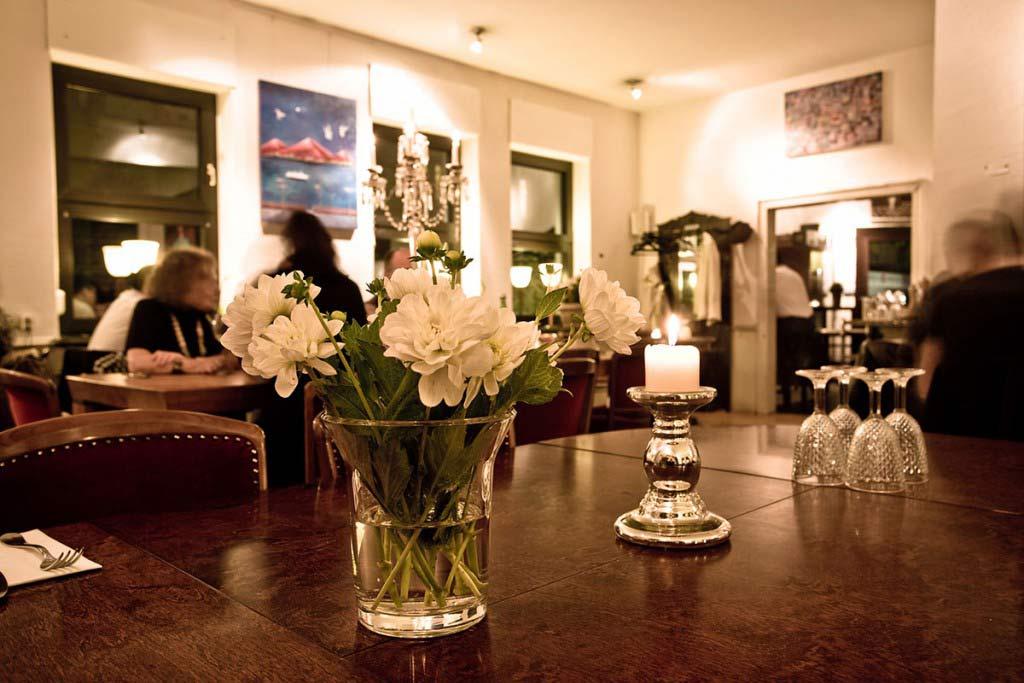 Innenansicht des Restaurants mit Blumen und Kerze geschmückter Tisch