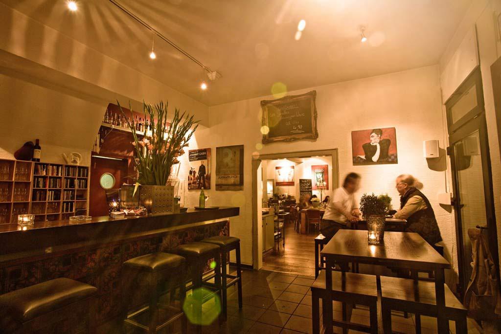 Blick in den Eingansbereich des Restaurants, mit Bar und Tischen
